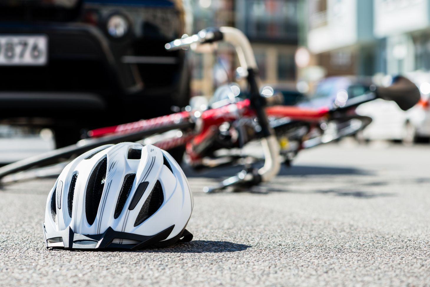 capacete e bicicleta caidos no chao com carro atras indicando acidente de transito