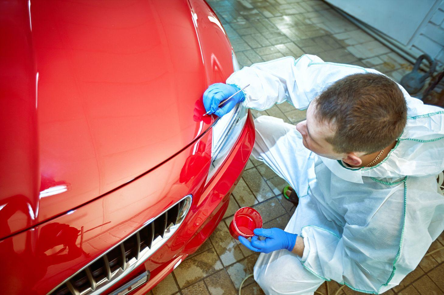 homem com pincel nas maos restaura pintura de carro vermelho