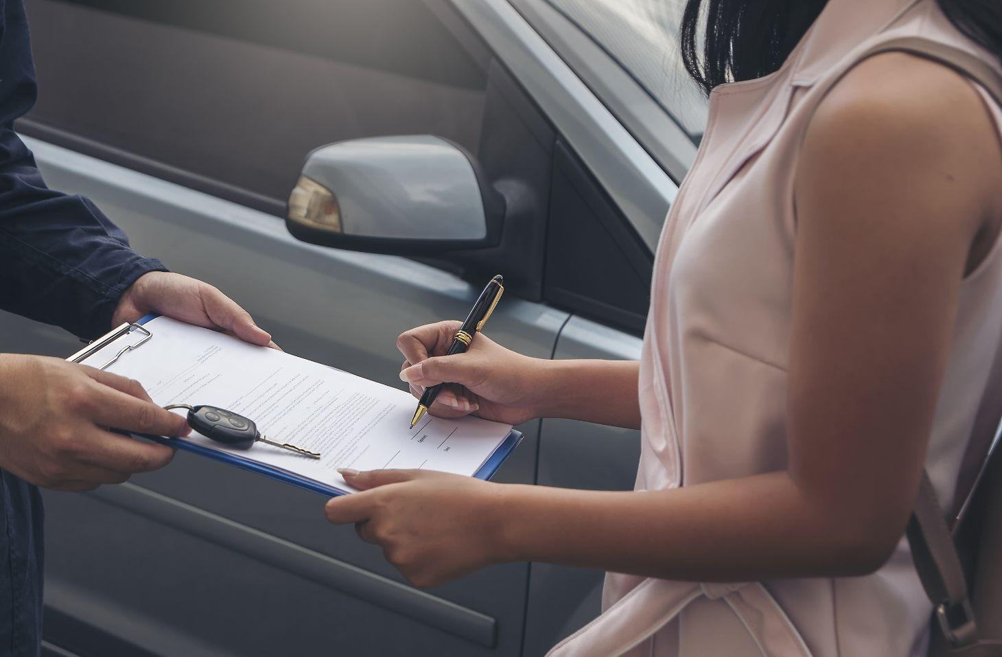 mulher com caneta na mao assina contrato de carro aluguel ou carro por assinatura e recebe chave do veiculo
