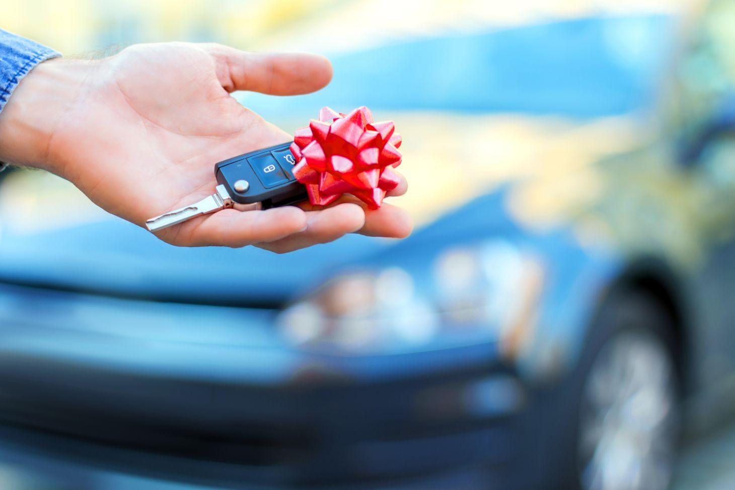 chave de carro tipo canivete com fita de presente vermelha e automovel desfocado no fundo