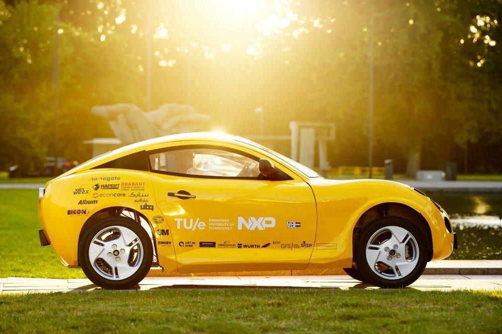 Carro elétrico feito de lixo amarelo visto de lado
