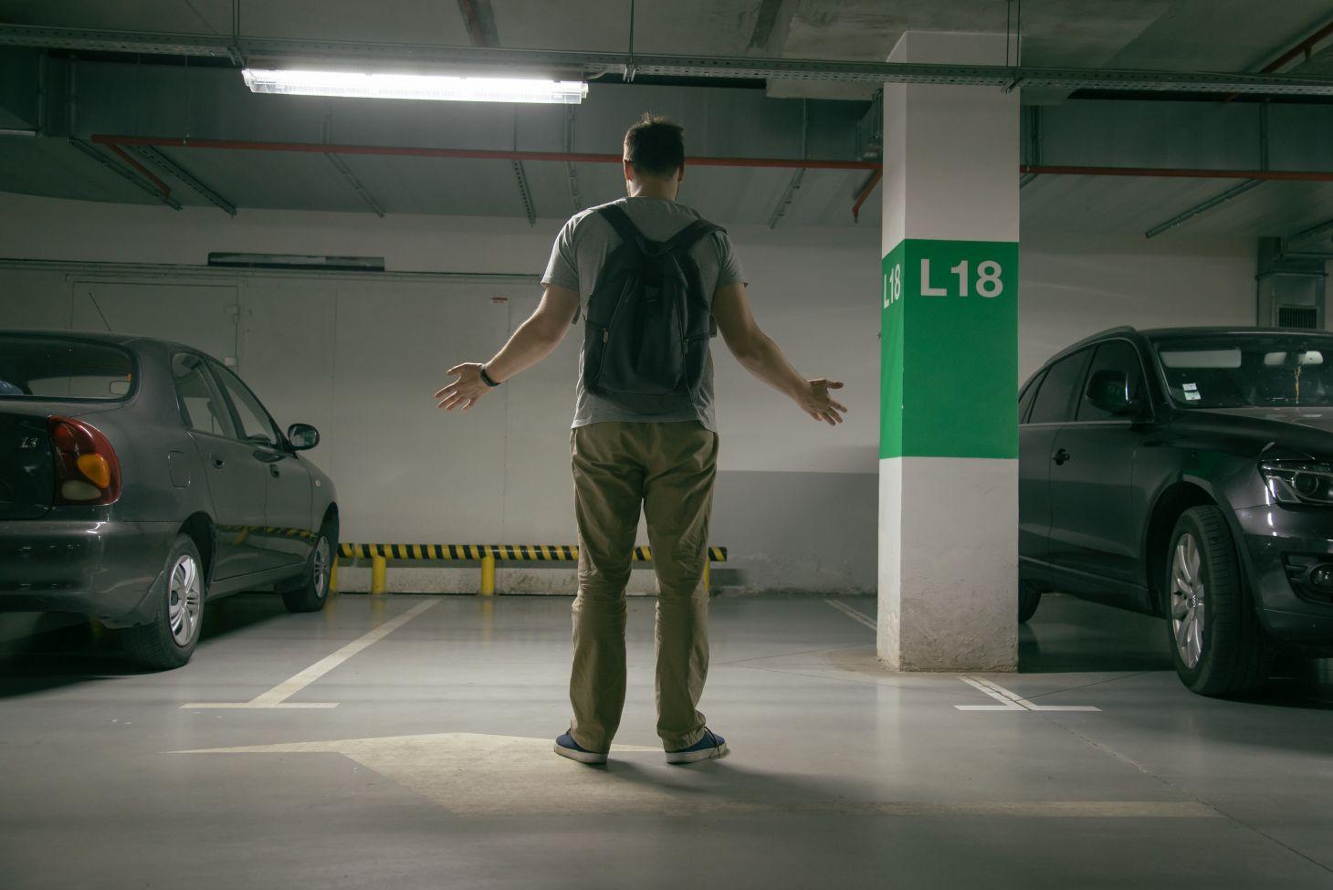 homem abre os braços em frente a vaga de estacionamento indicando que seu carro foi roubado
