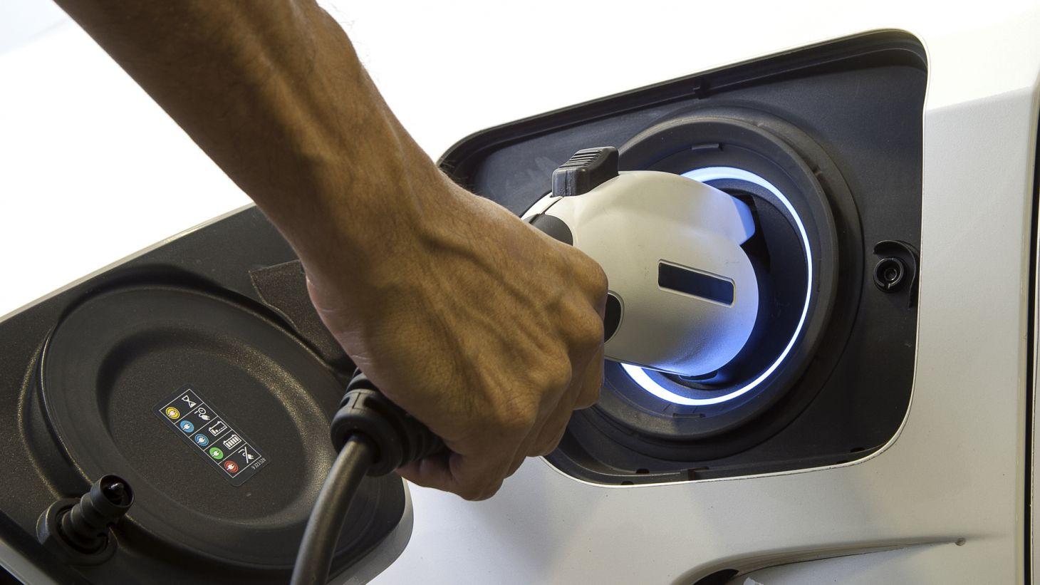 mao manuseando cabo carregar carro hibrido plug in eletrico