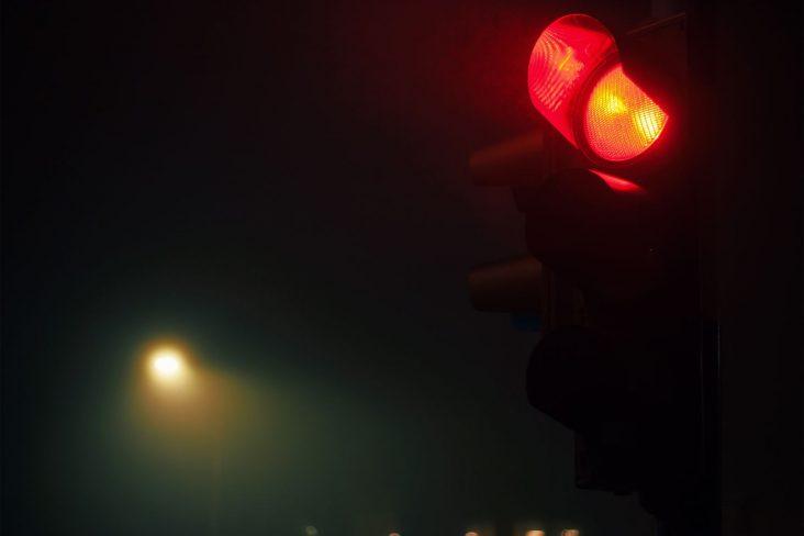 semaforo com sinal vermelho em noite escura shutterstock