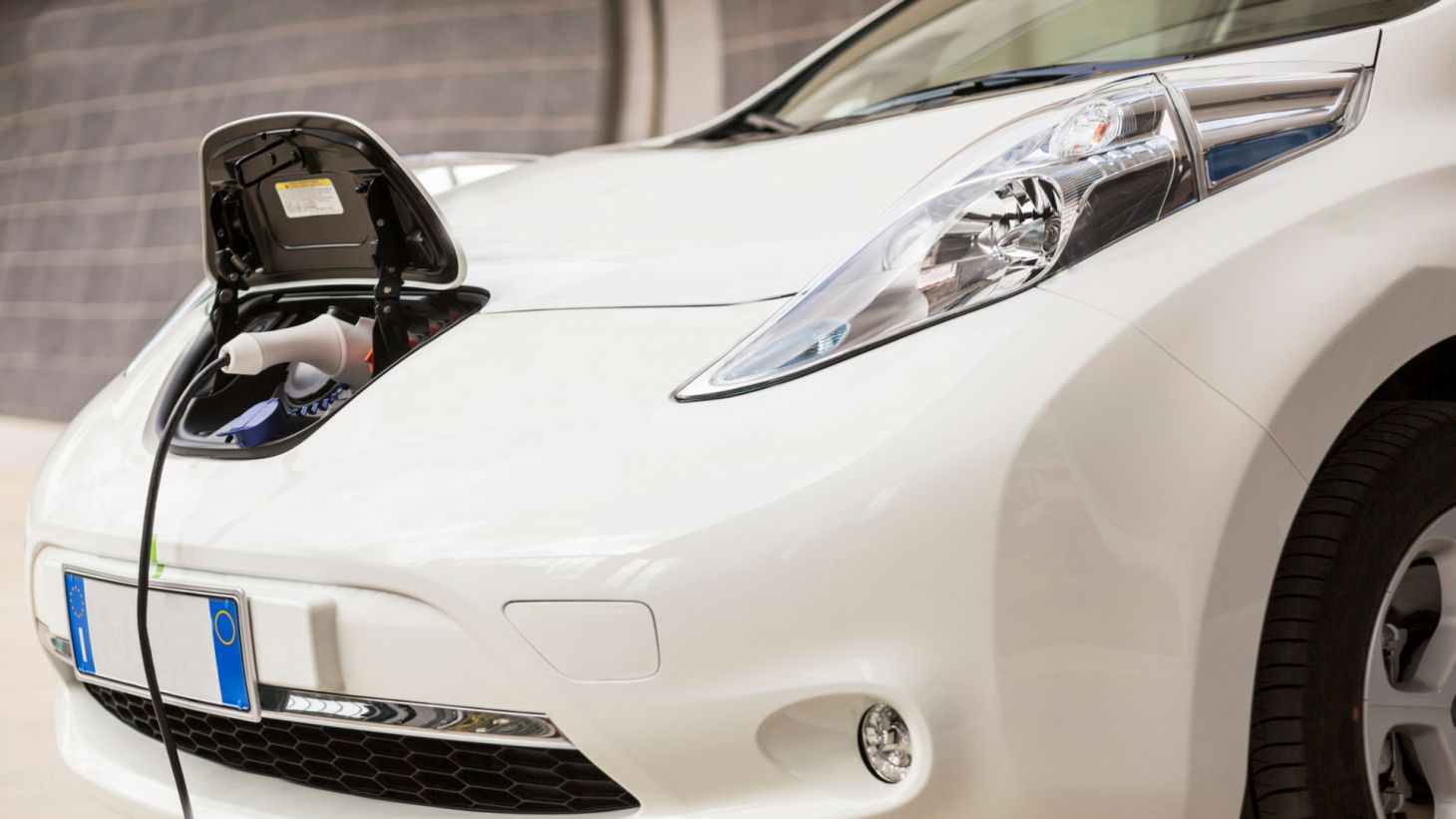 carro eletrico eletrificado sendo carregado ponto recarga dianteira detalhe