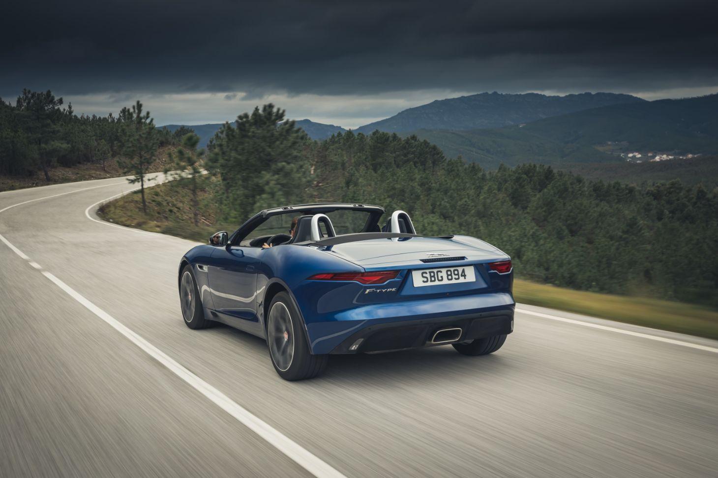 novo jaguar f type p300 conversivel azul visto de traz rodando em estrada