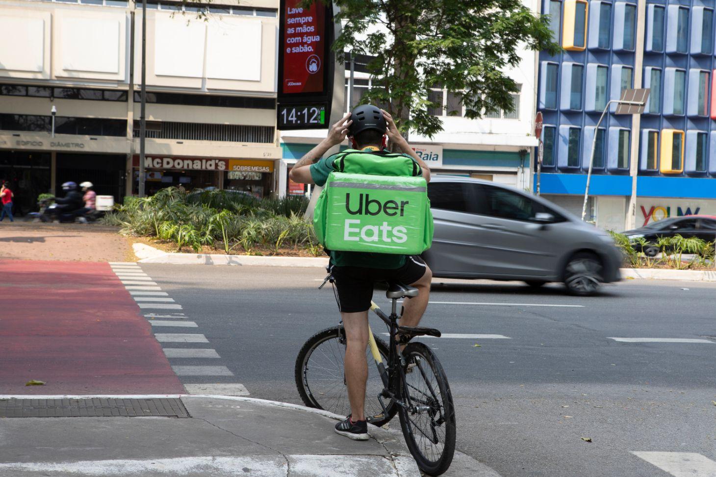 ciclista com mochila do uber eats aguarda para atravessar a rua shutterstock
