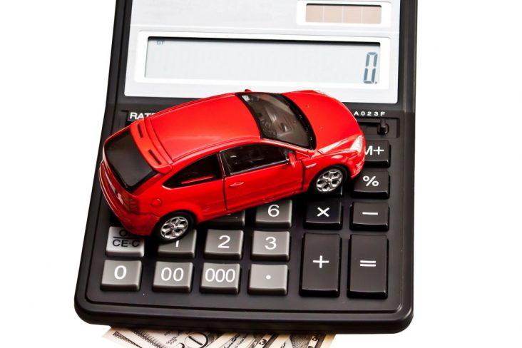 carrinho vermelho sobre calculadora e notas representando impostos taxas e triburos