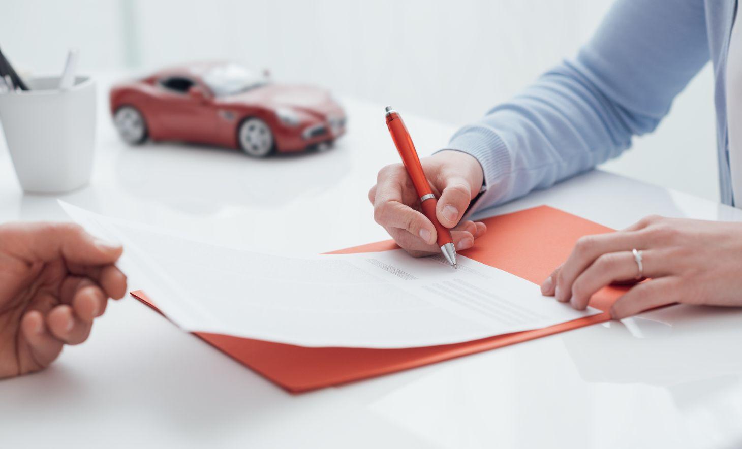 mulher de camisa social assina documento com carrinho de brinquedo vermelho ao fundo indicando contrato de carro por assinatura