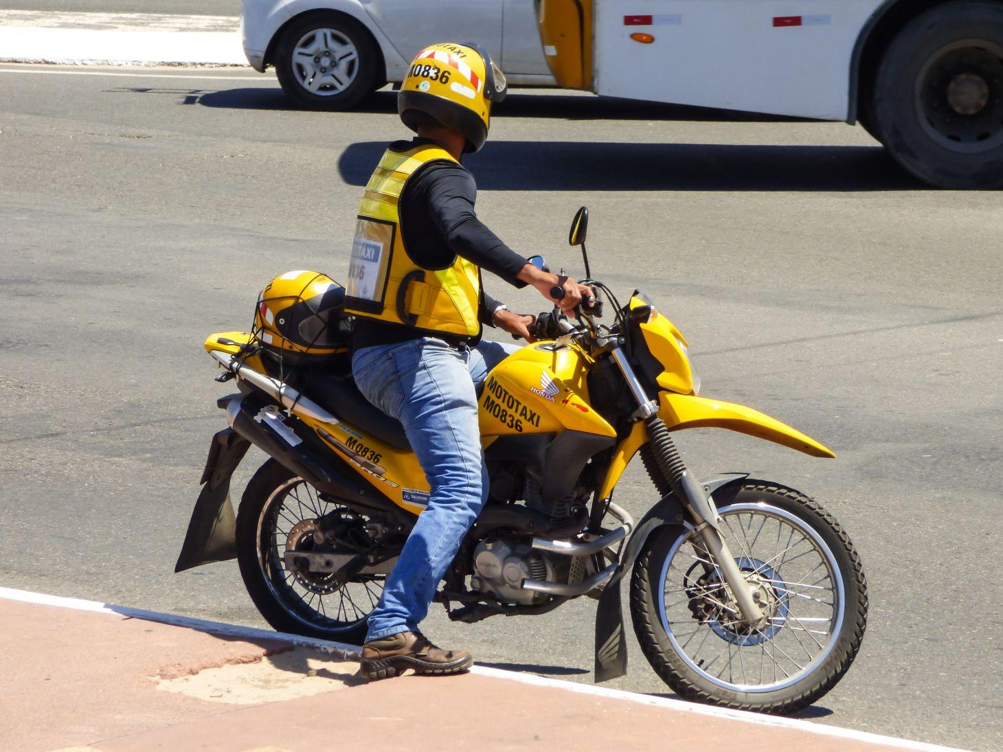mototaxista encostado no passeio olha para tras em salvador bahia