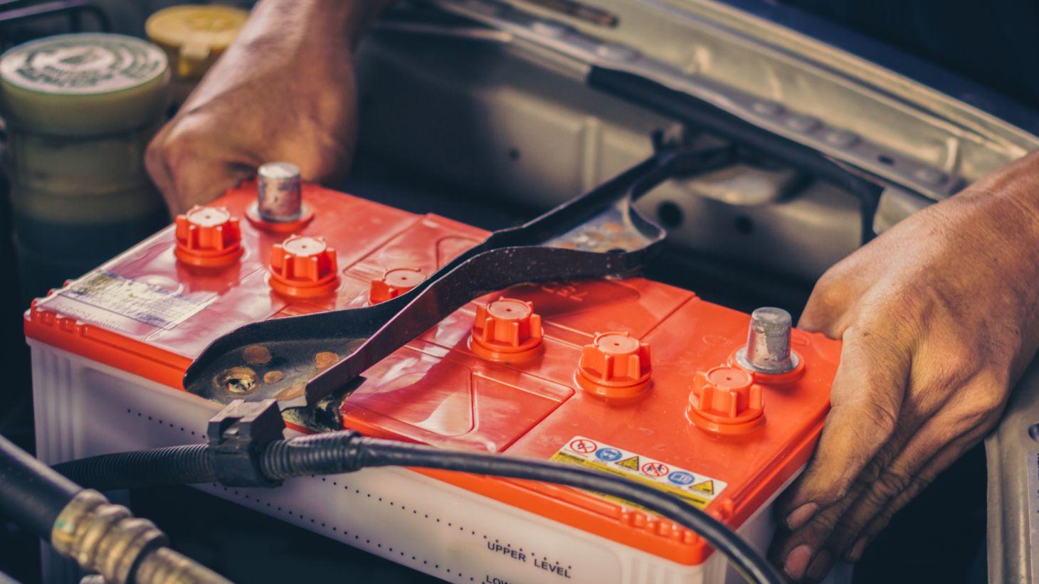 mecanico ajustando bateria do carro cofre motor
