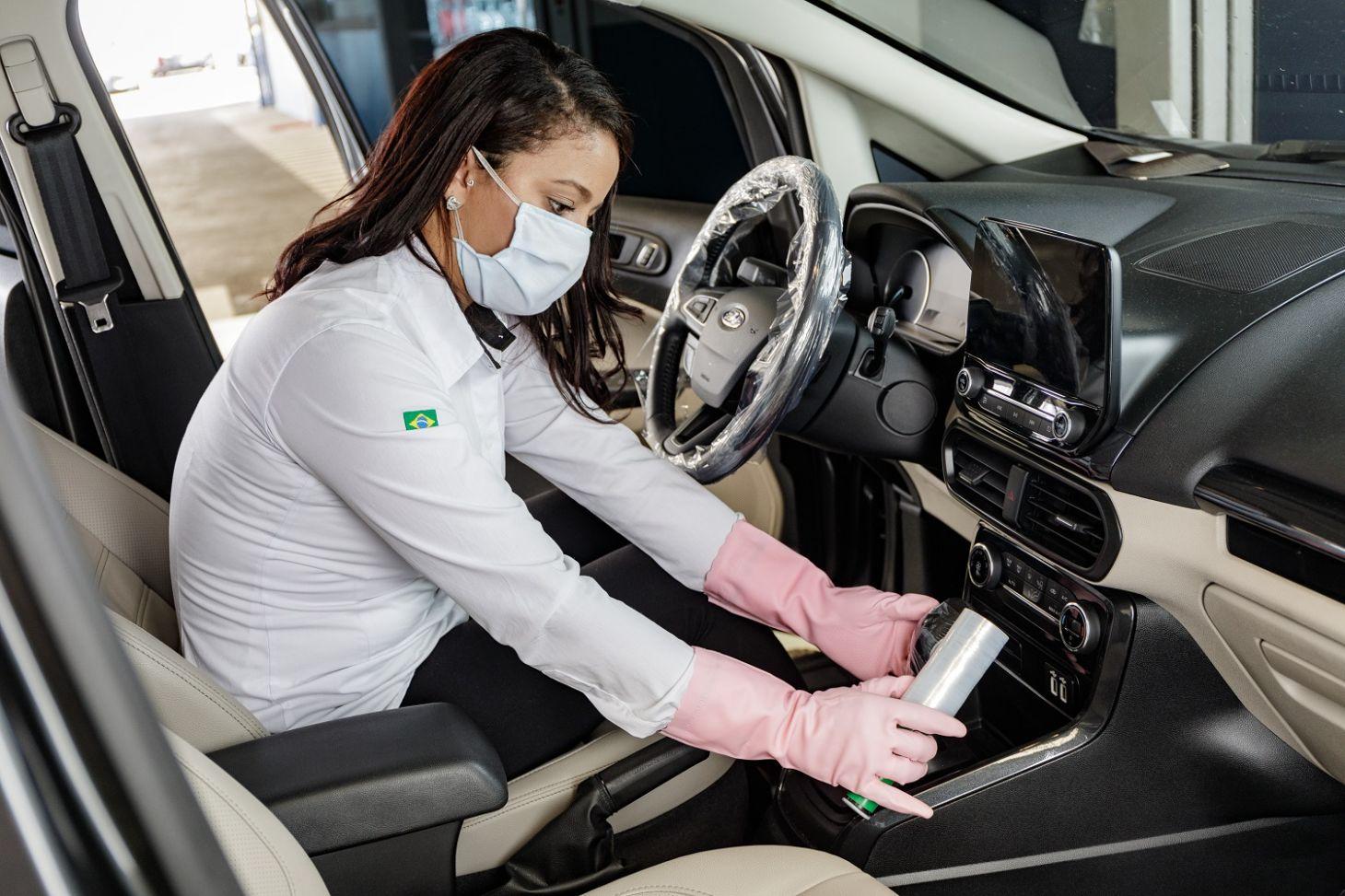 mulher de blusa social branca luvas rosa e mascara protege volante e cambio de carro ford