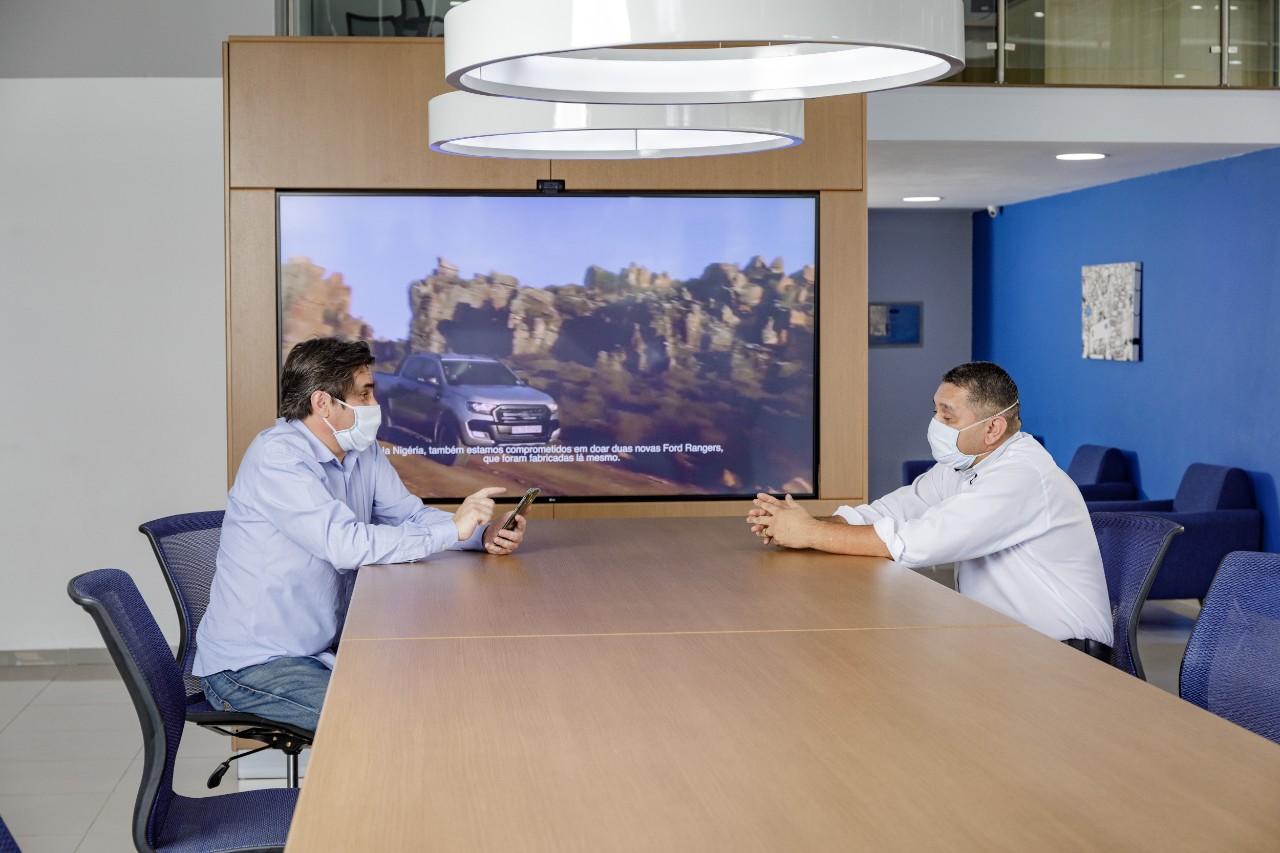 dois homens de camisa social e mascara em sala de reuniao da ford