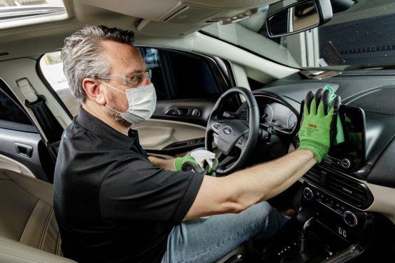 homem de blusa preta desinfeta painel de carro ford