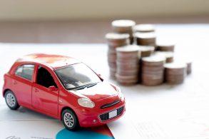 carrinho de brinquedo vermelho em frente a pilha de moedas representando impostos ligados a veiculos como ipva
