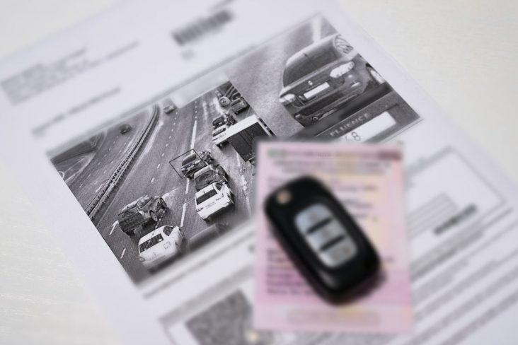 chave do carro desfocada sobre multa de velocidade