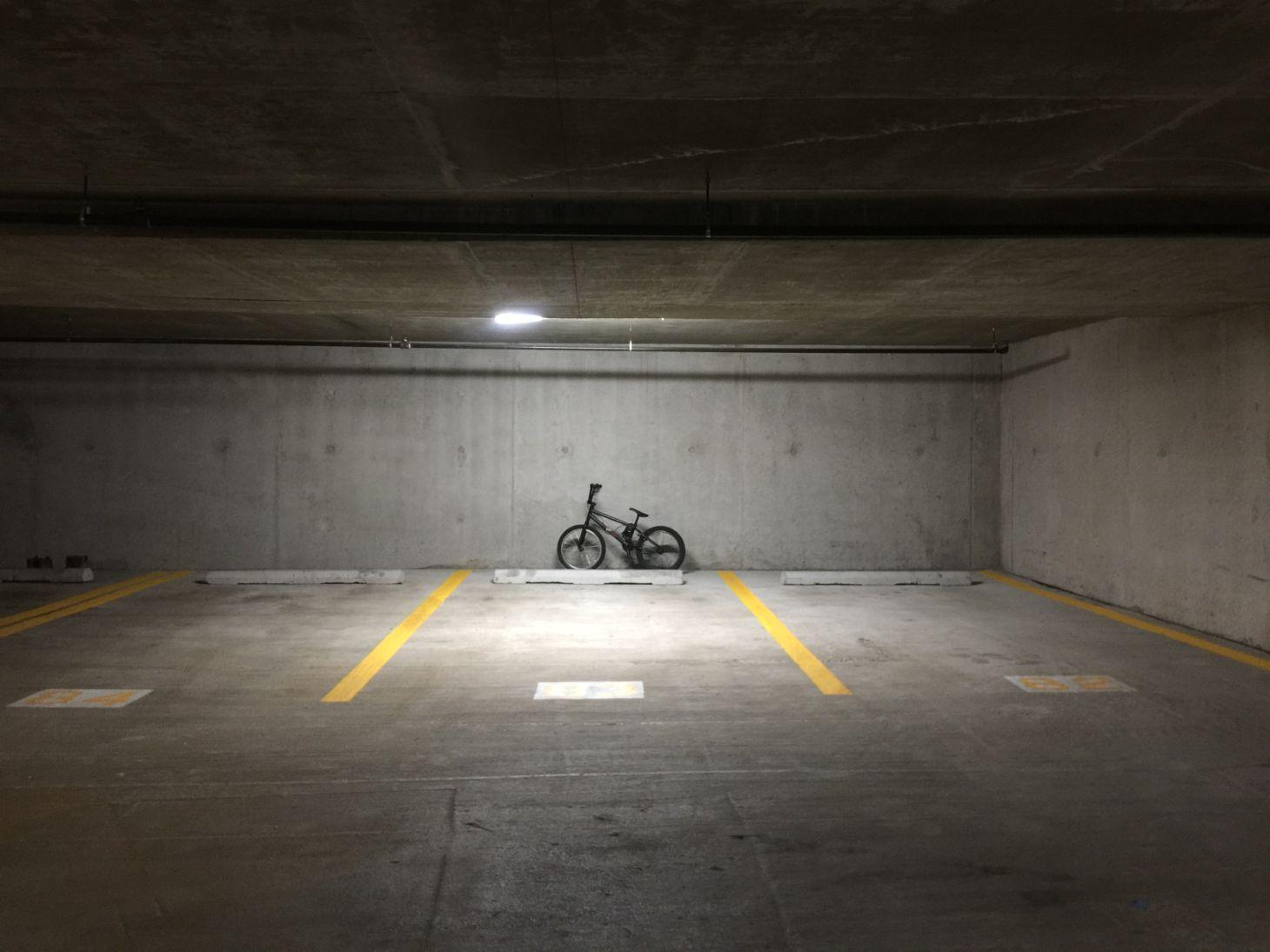 bicicleta encostada no fundo de uma vaga de garagem de condominio foto nicholas mazzaccaro unsplash