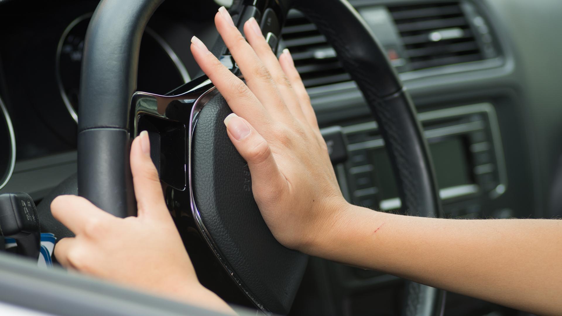 mao feminina acionando a buzina no volante de carro