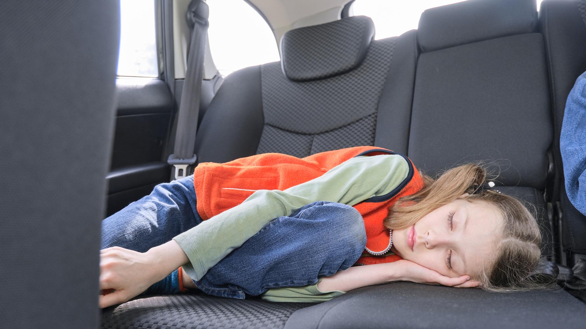 menina crianca deitada banco traseiro carro viagem viajar