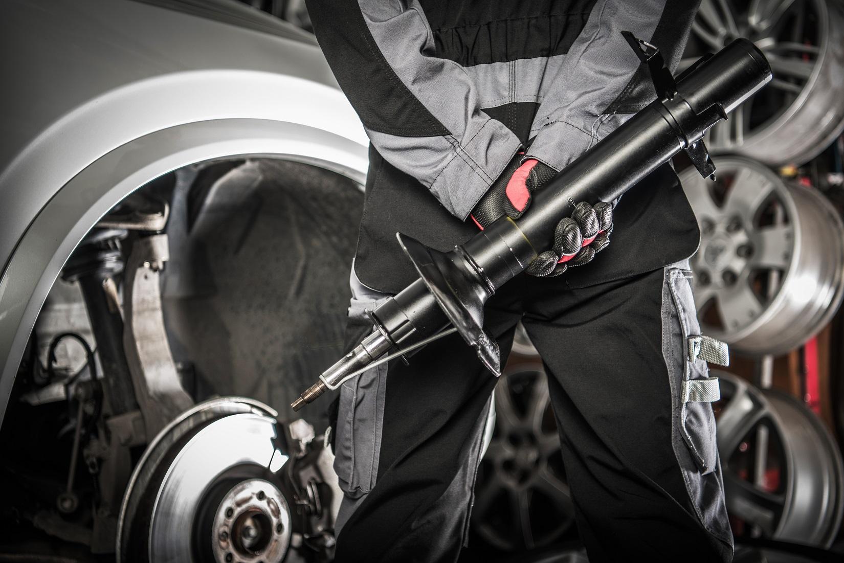 mecanico trocando amortecedor na suspensao de carro