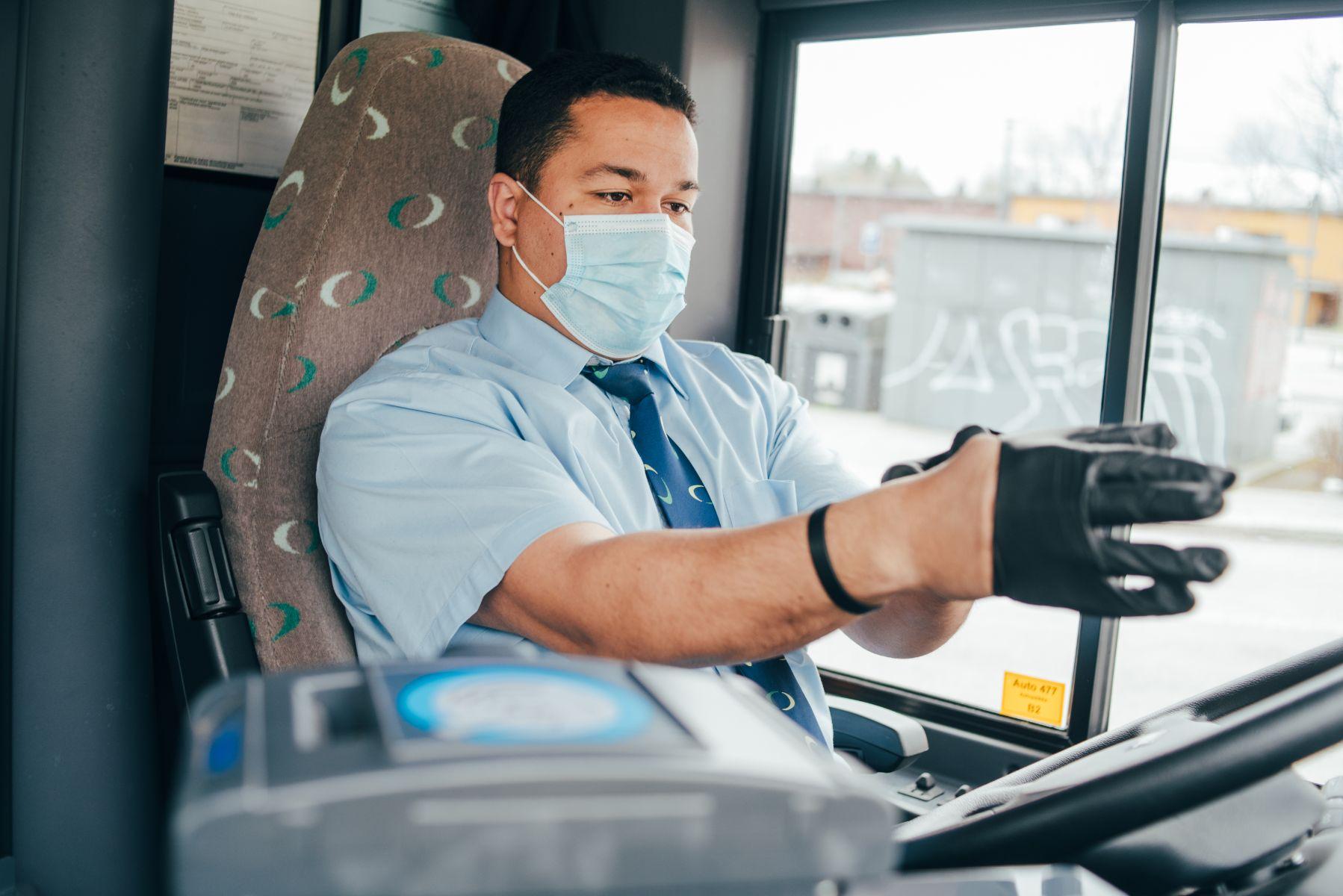 motorista profissional coloca luvas e mascara para se proteger da covid 19 em onibus destinado ao transporte de passageiros