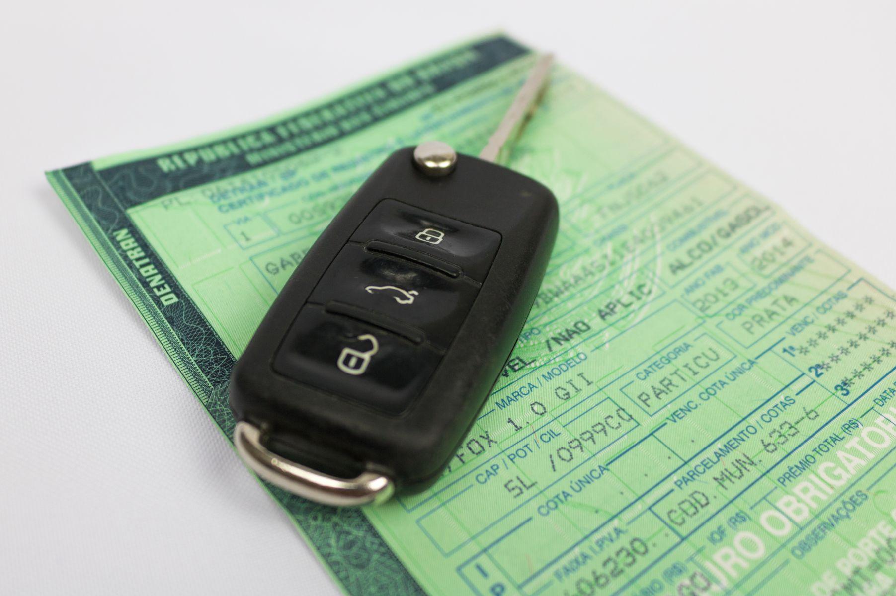 chave de carro em cima do documentocertificado de registro e licenciamento de veiculos