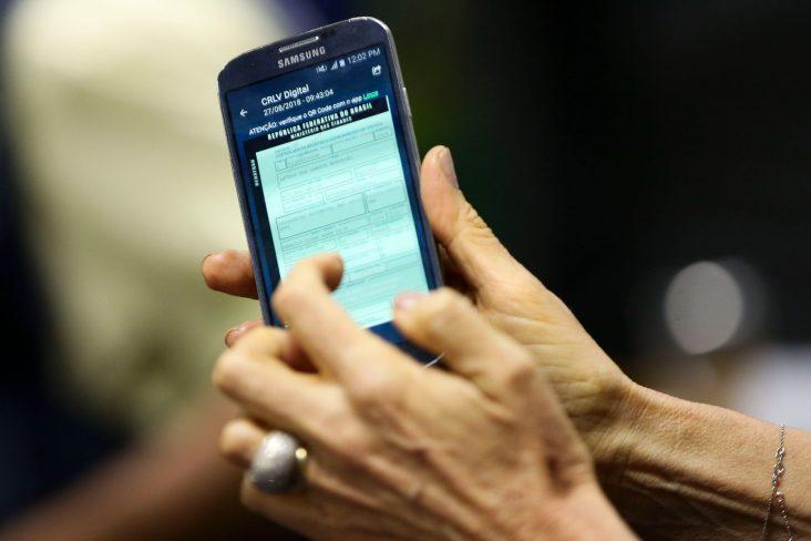 mulher segura celular com documento do carro digital crlv e aberto