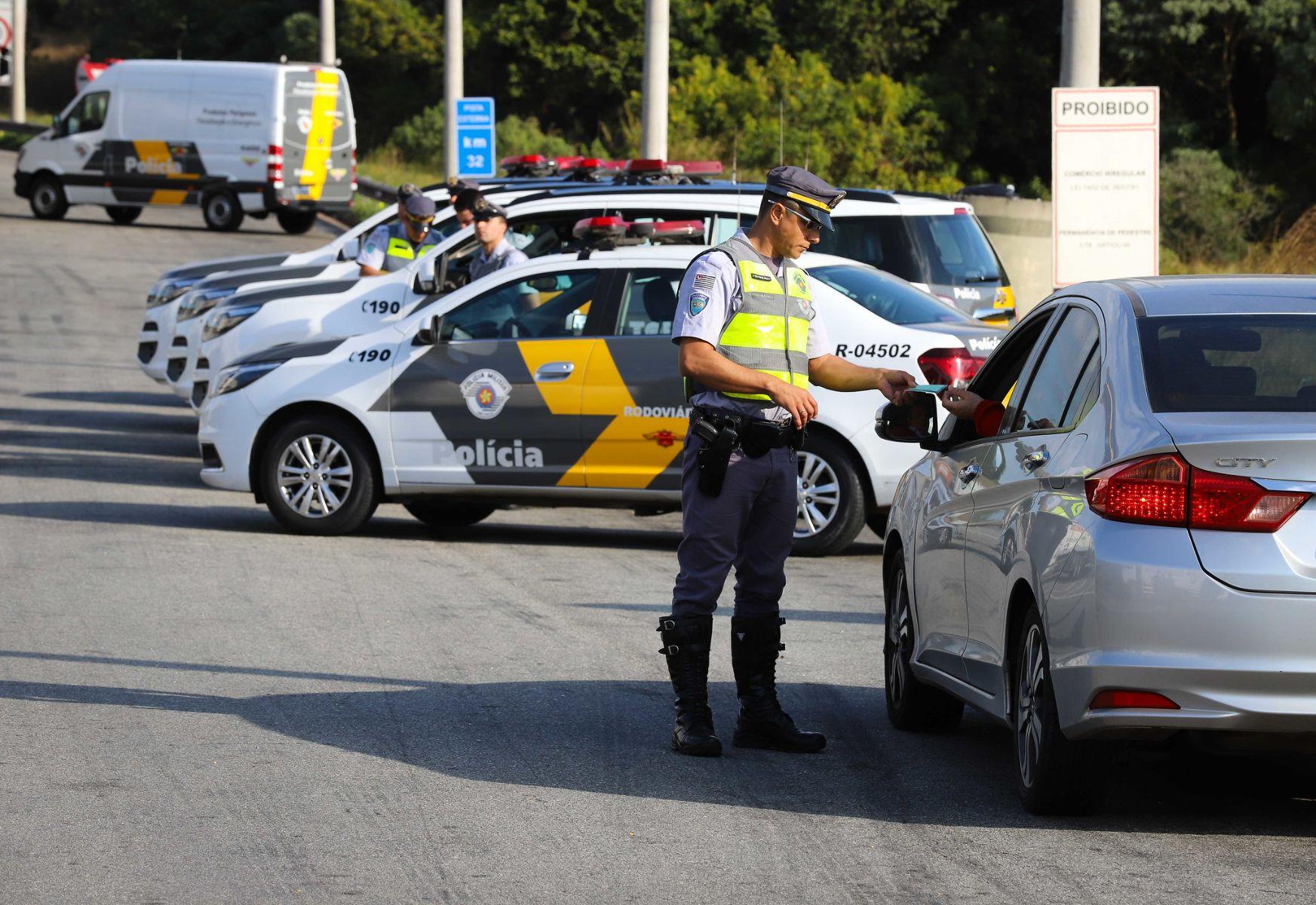 policial militar da cptran de sao paulo com documentos de motorista nas maos em fiscalizacao de transito com viaturas atras fotos governo de sao paulo