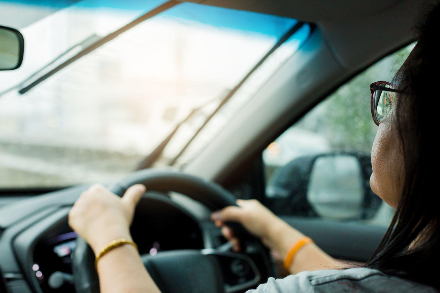 motorista mulher de oculos com as duas maos ao volante shutterstock