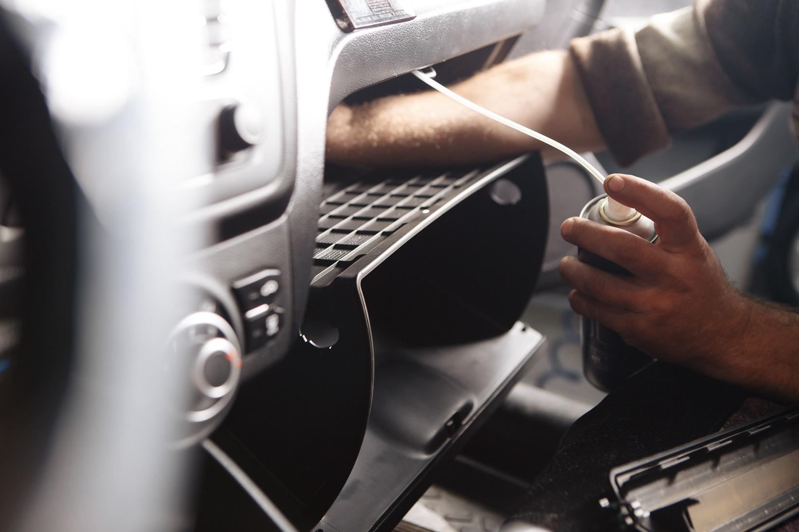 pessoa higieniza sistema de ar condicionado do carro com spray bactericida