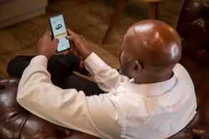 homem negro com celular nas maos abre aplicativo de carros por assinatura foto fca