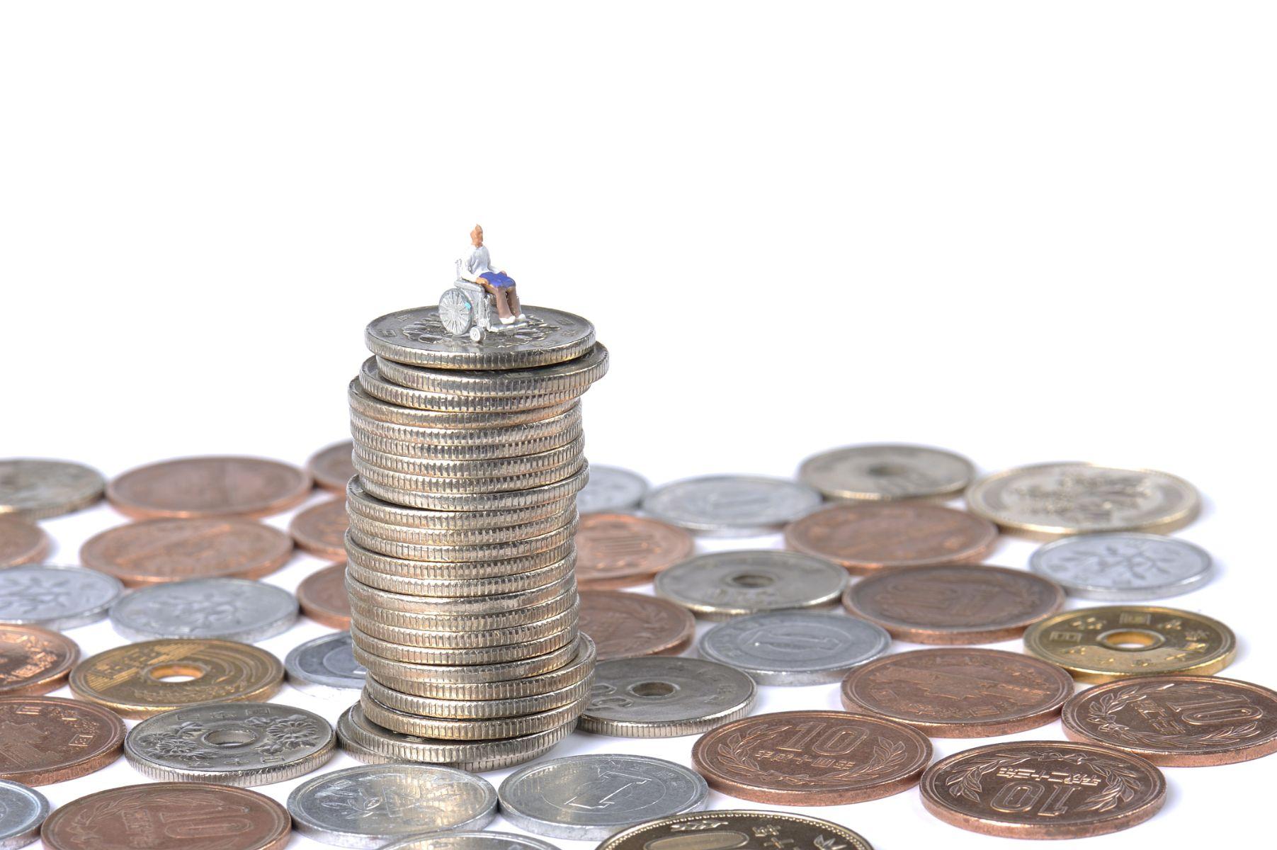 miniatura de um cadeirante ou pessoa com deficiencia pcd sobre moedas representando isenco de impostos como ipva ipi e icms
