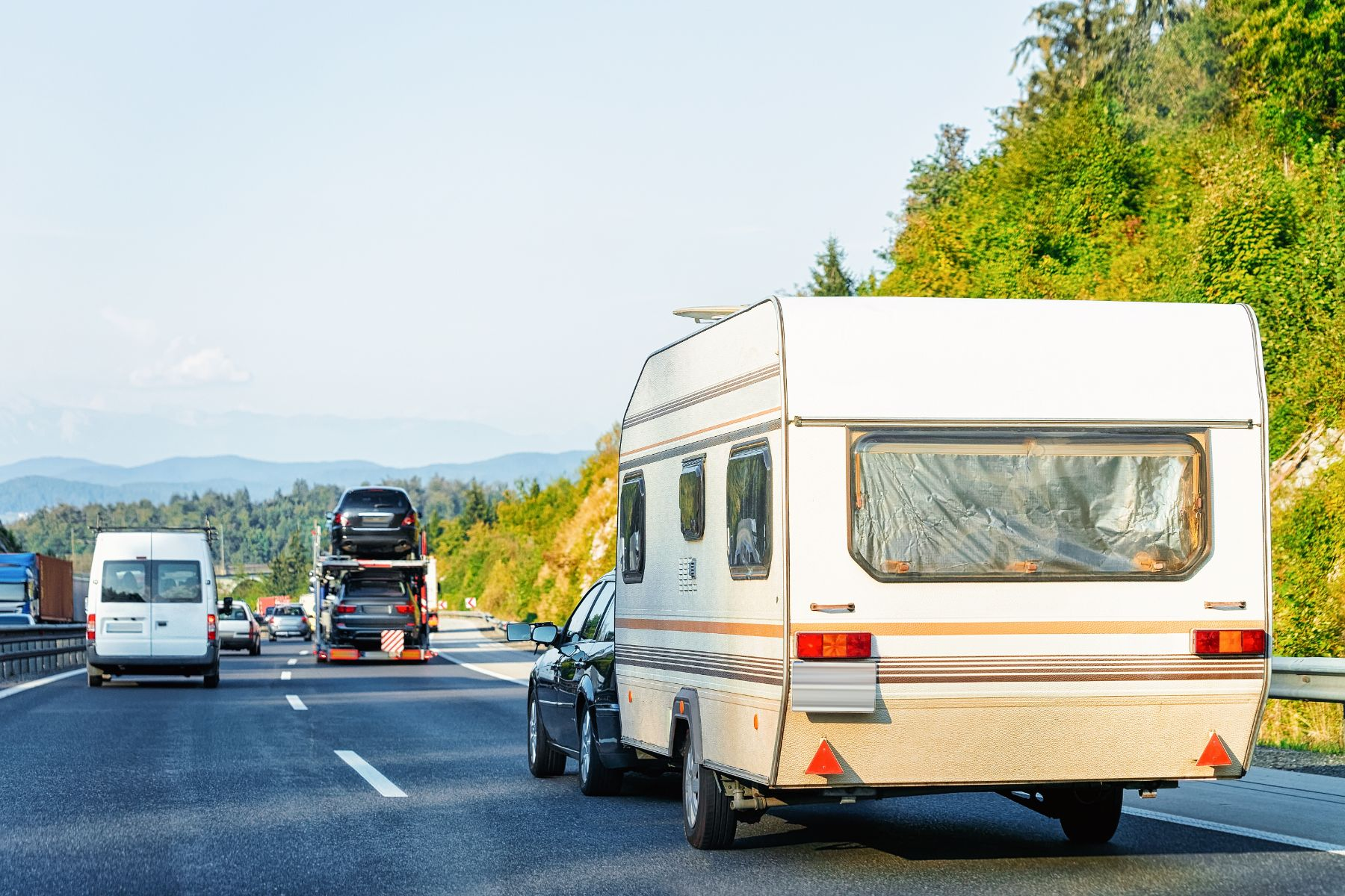 carro pequeno puxando trailer em estrada