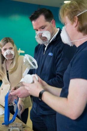 tres pessoas analisam mascara clara n95 desenvolvida pela ford