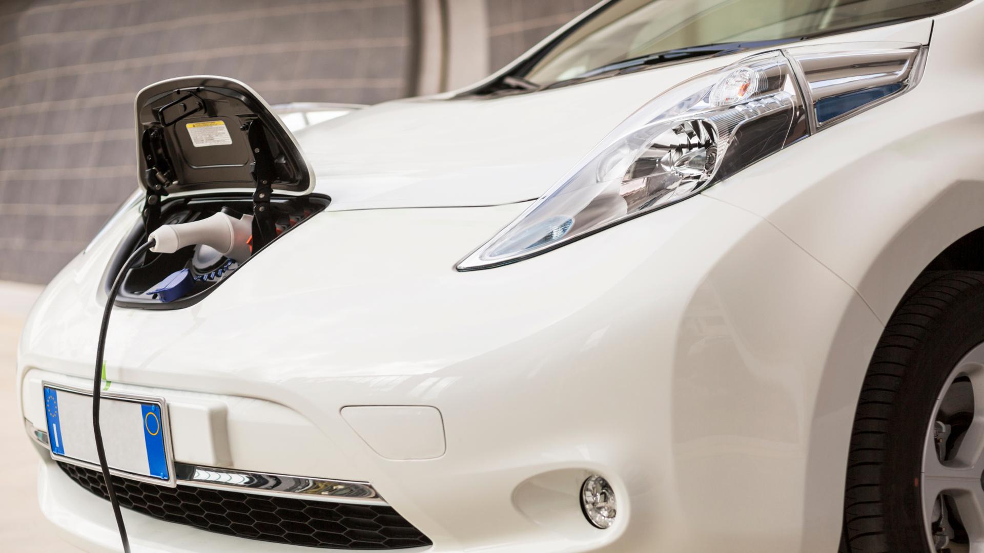 carro elétrico branco com carregador ligado na tomada