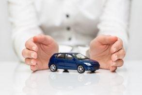 maos protegem carrinho de brinquedo azul representando protecao veicular e seguro automotivo