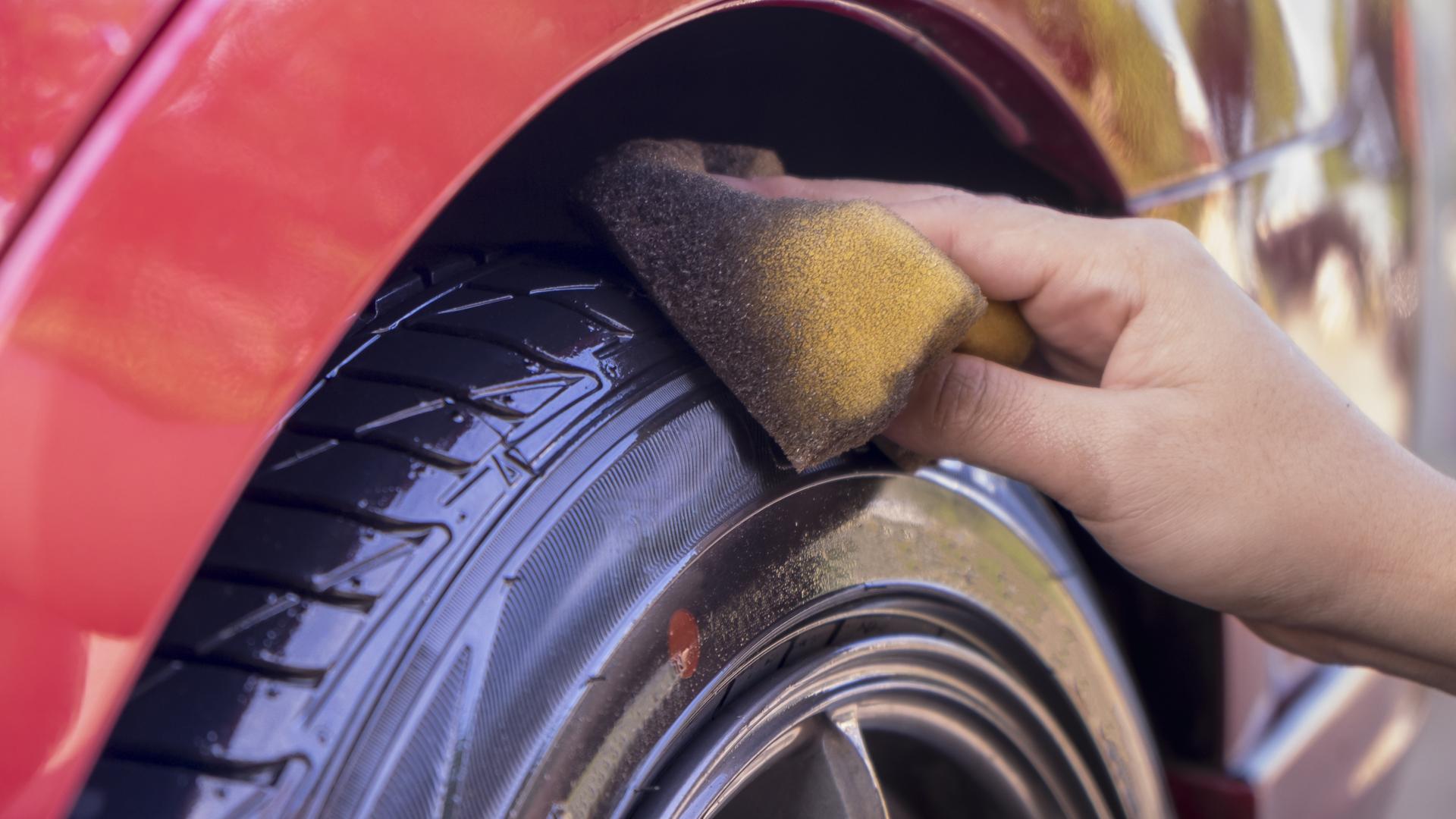 pessoa limpando pneu do carro pretinho shutterstock 529735651