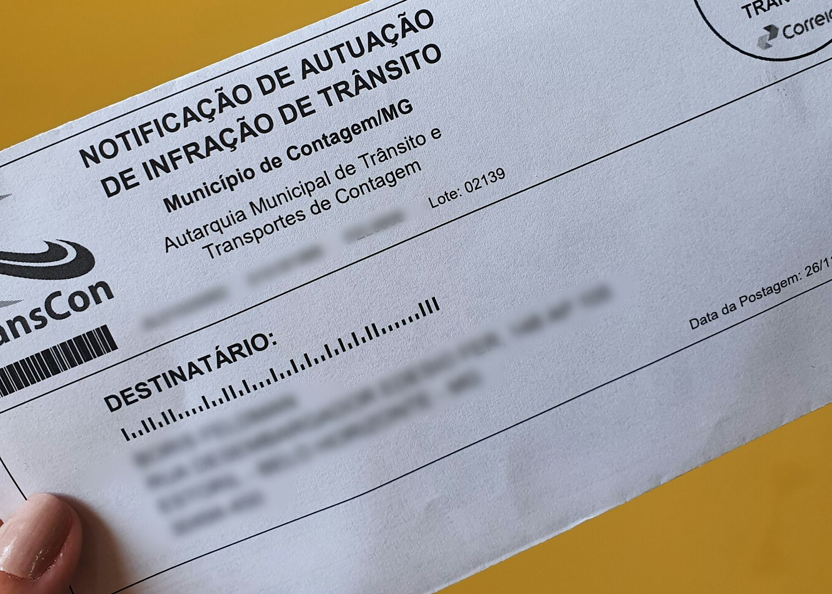 mulher segurando notificacao de autuacao de infracao de transito emitida pela transcon