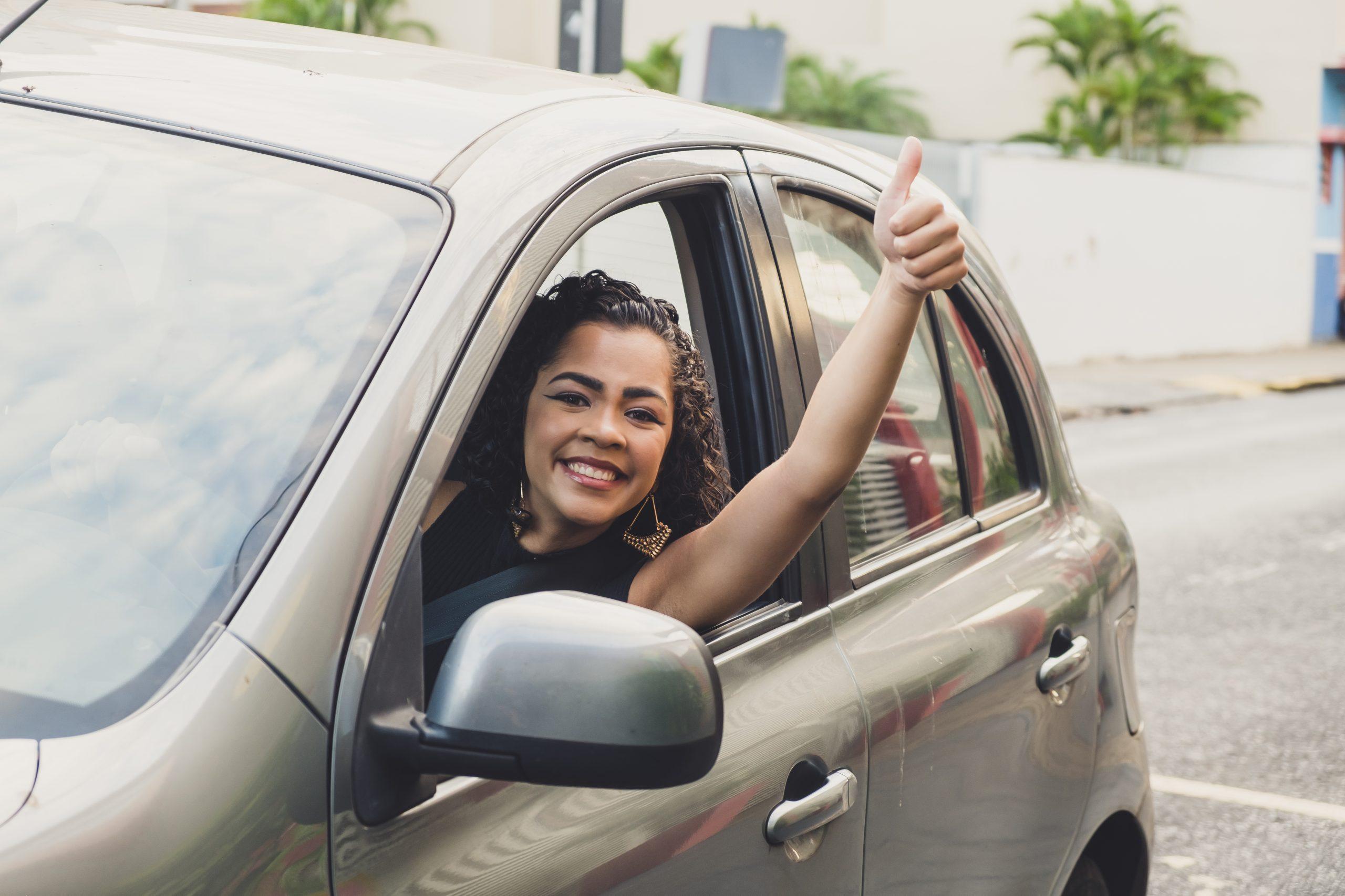 mulher ao volante com o braco para fora dando joia