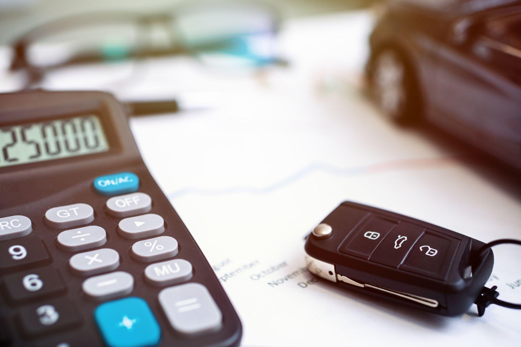 calculadora e chave de carro em cima de contrato