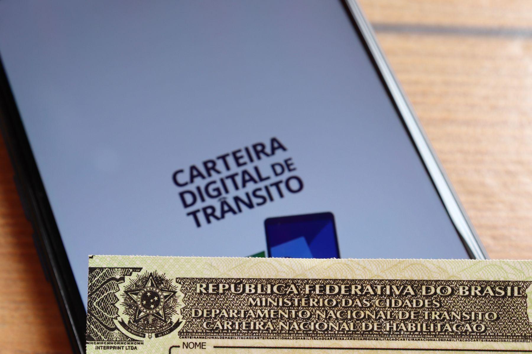 carteira nacional de habilitacao cnh em frente a celular com o aplicativo carteira digital de transito cdt aberto
