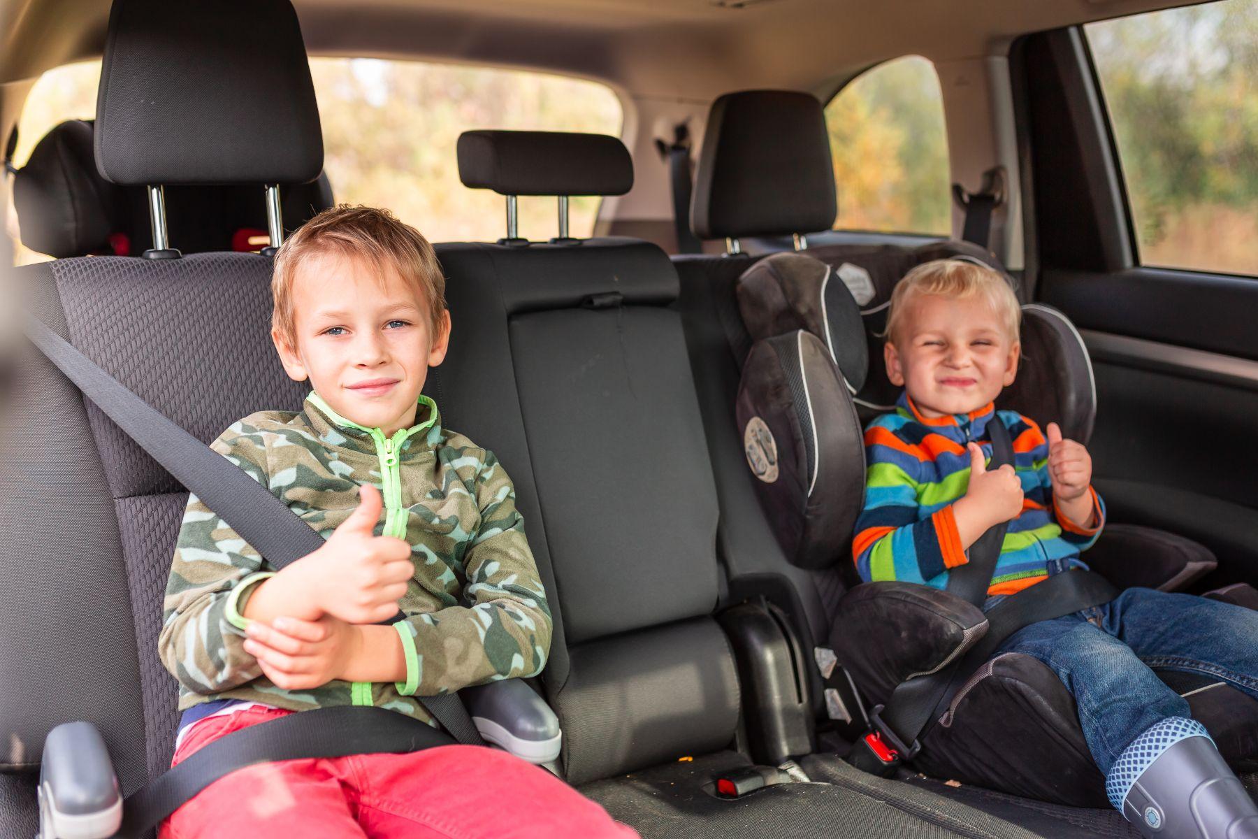 dois meninos no banco traseiro de um carro um na cadeirinha e outro no booster