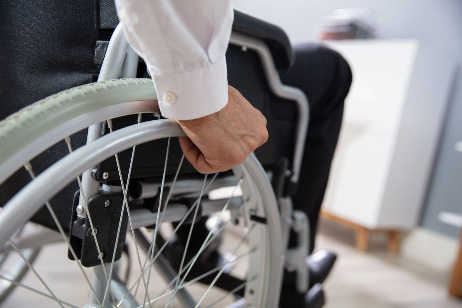 mao de uma pessoa com deficiencia pcd sobre a roda de uma cadeira de rodas