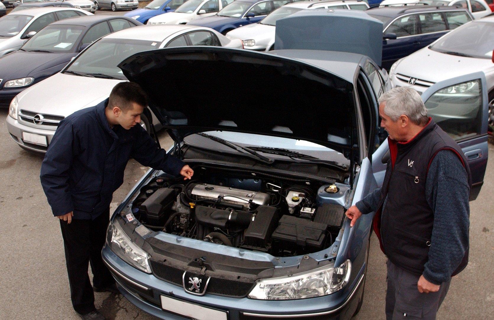 dois fomens verificam carro usado com capo aberto