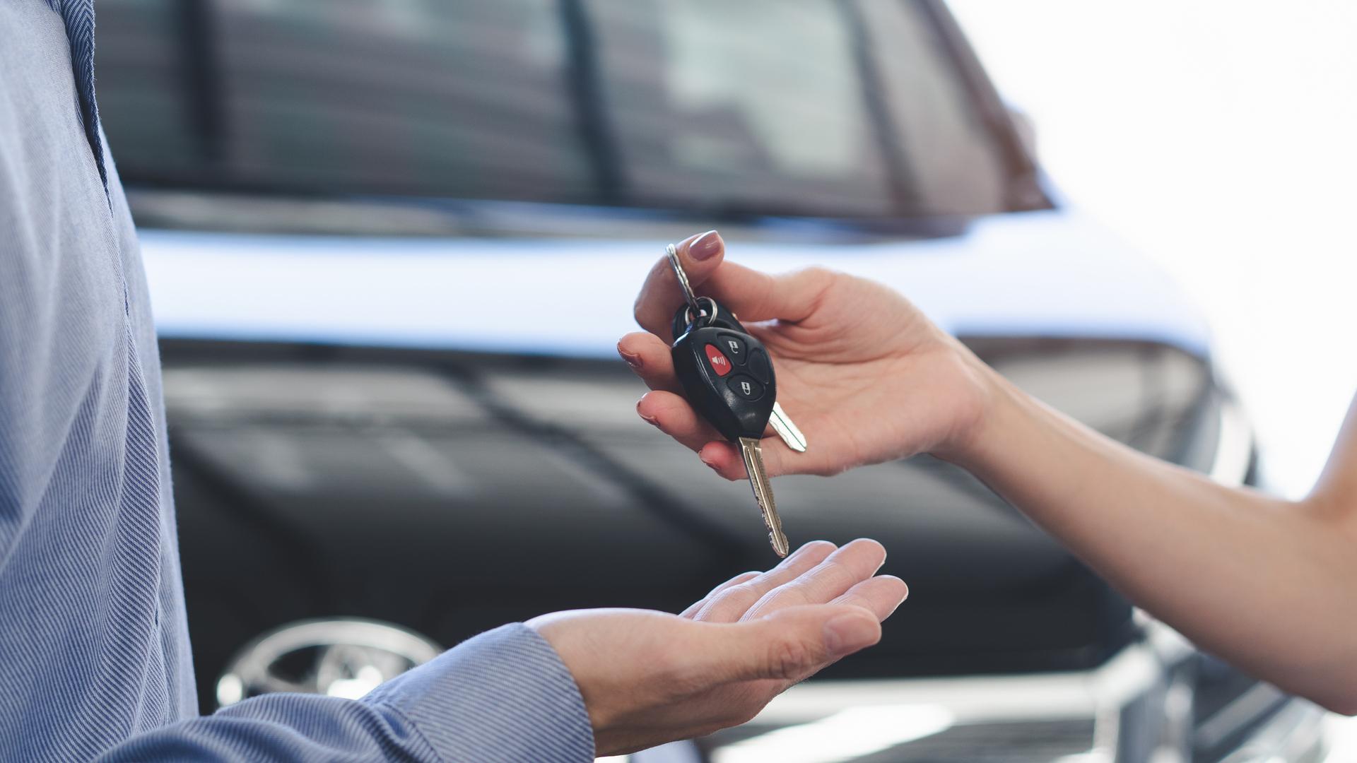 mao de mulher entrega chave de carro para mao de homem