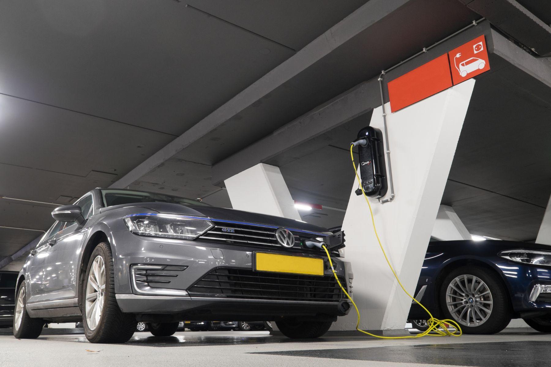 volkswagen cinza em garagem com carregador para carros eletricos