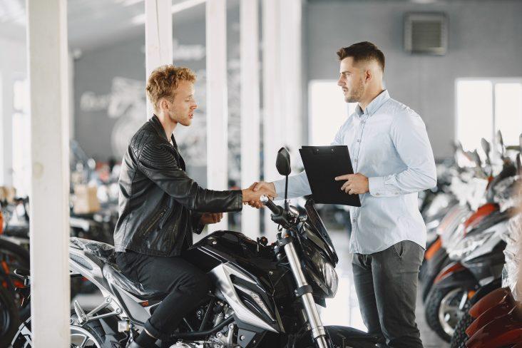 homem de jaqueta preta cumprimenta vendedor de loja de moto de camisa branca