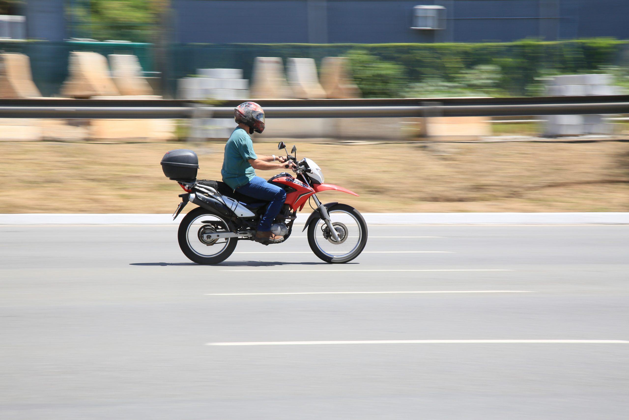 motociclista conduzindo moto vermelha com bagageiro em via expressa de salvador