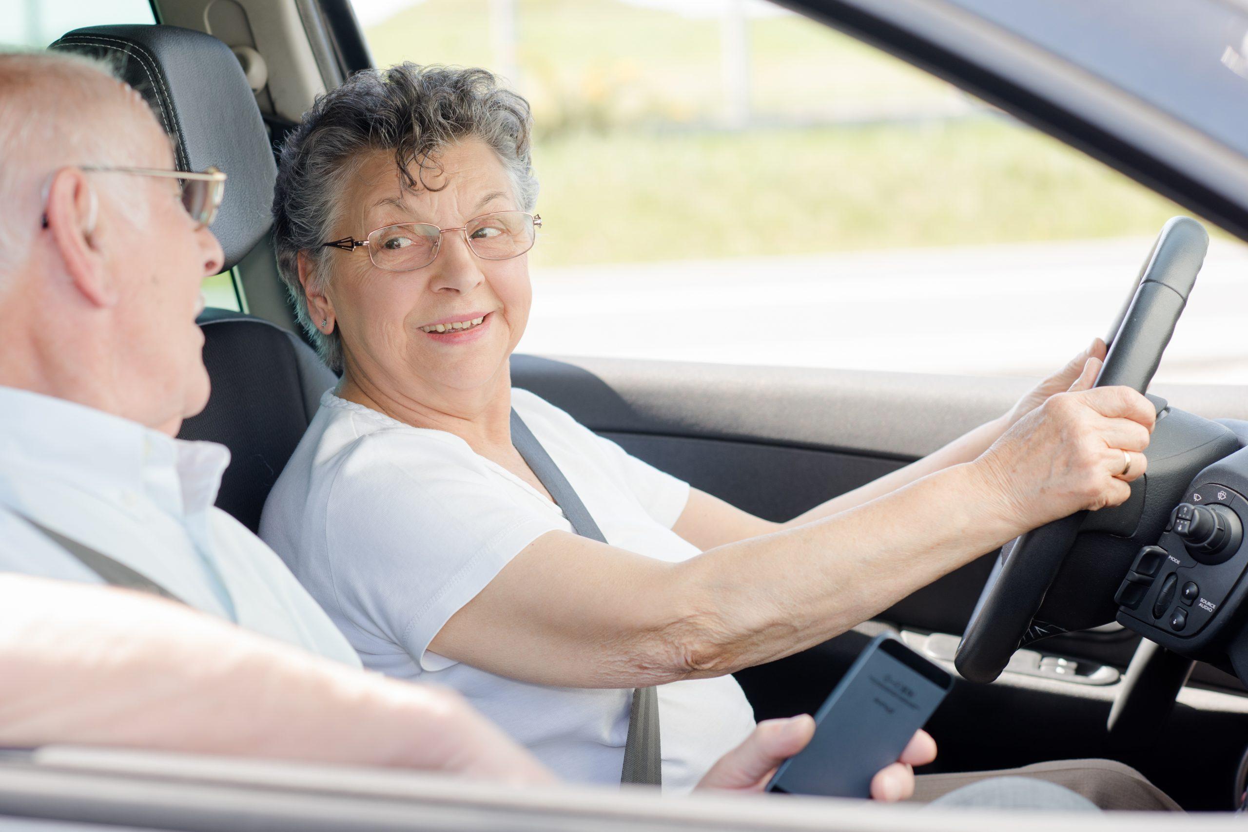 mulher idosa ao volante de carro com passageiro idoso ao lado