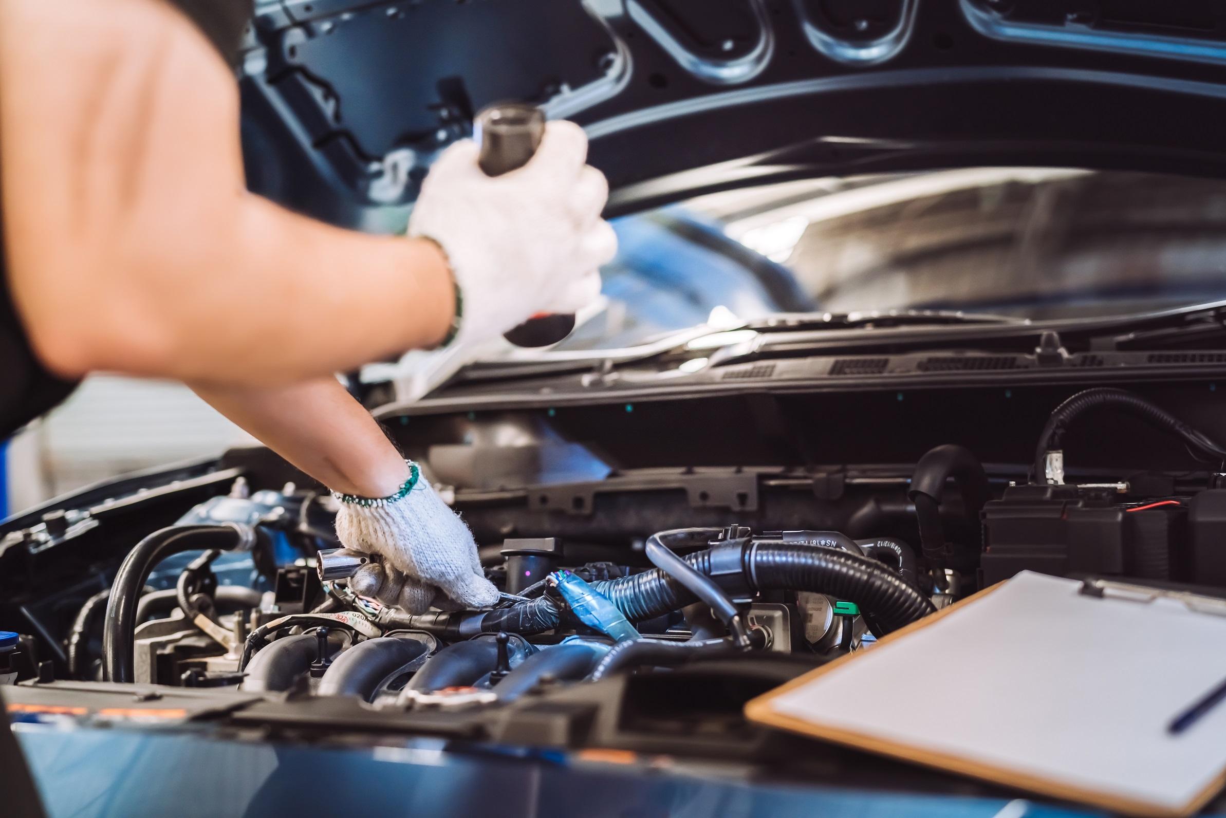 mecanico examina motor de carro em oficina